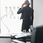 Frau steht am Bürofenster und telefoniert
