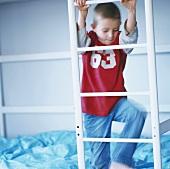 Kleiner Junge klettert Leiter am Stockbett hoch