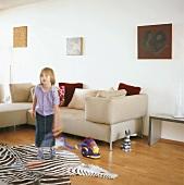 Mädchen spielt mit einem Kinder-Staubsauger im Wohnzimmer