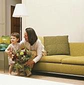 Mutter und Kind mit einem Blumenstrauss im Wohnzimmer