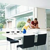 Mutter und Tochter mit Kuchen am Tisch in einer Wohnküche