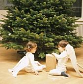 Mädchen und Junge packen Weihnachtsgeschenk aus