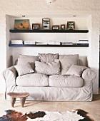 Gemütliche Couch in einer Nische, darüber zwei einfache Wandregale