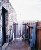 Einfache Dusche im Aussenbereich eines rustikalen Steinhauses mit Sichtschutz aus Holz