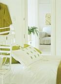 Gemütliches Holzbett im Shabby Chic Stil, gemixt mit frischen Grüntönen, dahinter eine weiße Couch