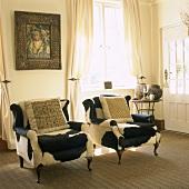Zwei mit Kuhfell überzogene, antike Sessel und ein Gemälde in einem hellen Wohnraum
