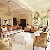 Sitzmöbel und Dekoelemente verschiedener Epochen in einem Wohnraum mit kassettierter Decke und griechischer Säule