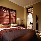 Einladendes Doppelbett in einem Schlafzimmer mit afrikanischem Flair