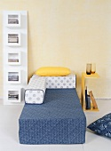Moderne Schlafzimmerausstattung mit Regal, Beistelltisch und Bett in Gelb, Blau und Weiß