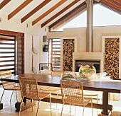 Großer Esstisch und Kamin in einem Raum mit schräger Holzbalkendecke und verglastem Giebel