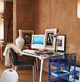 Arbeitsecke mit Glasschreibtisch vor einer braunen Wand