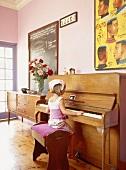 Ein Kind am Klavier in einem Zimmer mit Stuckdecke und Dielenboden