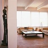 Minimalistisch eingerichtetes Wohnzimmer mit großem Langfenster und Dielenboden