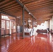 Designermöbel in einem Loft mit Holzbalkendecke, Stahlträgern und Dielenboden aus Kirschholz