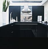 Moderne Küchenzeile in Schwarz mit Dunstabzug aus Edelstahl und Blechabdeckung