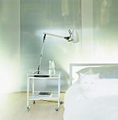Schlafraumausschnitt mit minimalistischen Aluminiummöbeln und weisser Katze auf dem Bett