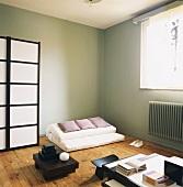 Wohnraum im japanischen Stil mit Futon und Paravent
