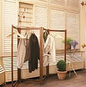 Einfache Klappgarderobe vor einer Wand mit geschlossenen Fensterläden