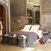 Großer Spiegel am Kopfteil eines Doppelbettes und drei moderne Beistelltische aus Stahl am Fussteil