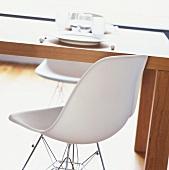 weiße Designerstühle an einem schlichten Holztisch