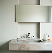 Ein Waschtisch aus Naturstein mit einfachem Badezimmerspiegel vor einer Wandnische