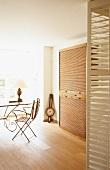 Blick durch eine geöffnete Holzjalousietür in das Arbeitszimmer mit Jugendstilstuhl und Rolladenschrank