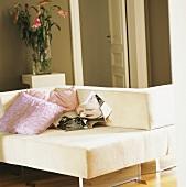 Ein weisses Doppelsofa mit Zierkissen vor einer gläsernen Blumenvase