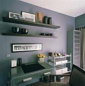Ein modernes Arbeitszimmer in dunklen Farben mit schwarzen Wandboards und antikem Schreibtisch