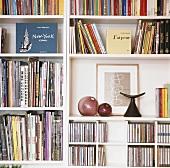 Ausschnitt eines weissen Regals mit Büchern, CD's und Deko