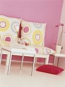 Durch die schlichten Möbel und eine rosa Wand mit abgestimmten Wohnaccessoires entsteht ein modernes Retrogefühl