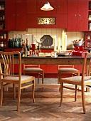 Eine gemütliche Wohnküche mit roten Schrankelementen und einem großen, alten Holztisch