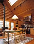 Der alte Bauerntisch und der Holzofen tragen zur warmen Atmosphäre in der Wohnküche des gemütlichen Holzhauses bei