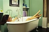 Woman lying in a bathtub