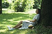 Woman sitting on grass leaning against a tree