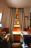In dem 20er Jahre Badezimmer mit Holzvertäfelung und Blümchentapete ist die Badewanne durch einen Vorhang abgetrennt