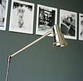 Eine Tischleuchte aus Metall vor einer Serie von Schwarzweiss Fotografien