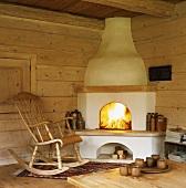 Ein traditioneller Eckkamin aus Lehm und ein Schaukelstuhl in einer urigen Holzhütte