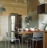 Die moderne Kücheneinrichtung stellt einen spannenden Kontrast zu der zerfallenen Wand dar