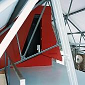Roter Einbau zwischen Stahlträgern auf der Galerie eines Lofts mit Backsteinwänden