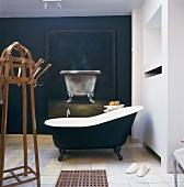 Ein antiker Garderobenständer aus Holz und eine dunkelblaue, freistehende Badewanne