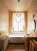 Prunkvoll und zugleich schlicht wirkt dieses Badezimmer mit Marmorbadewanne und aufgemalten Vorhängen