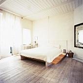 Das Bett in dem spartanisch eingerichteten Schlafzimmer vereint verschiedene Stile und Materialien zu einem Ganzen