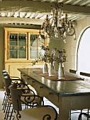 Ein edler Lüster und dezente Tischdeko schmücken den antik eingerichteten Essraum des Landhauses