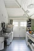 Eine spartanische Küchenzeile mit Küchengeräten und schöne Vintagemöbel in einem weissen Anbau