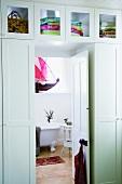 Zwischen zwei Kleiderschränken gibt die geöffnete Tür den Blick auf das dahinterliegende Badezimmer frei