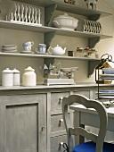 Küchenschrank und Wandboards mit Geschirr in einer romantischen Holzküche