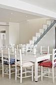 Ein weisser Landhausesstisch vor einer modern-minimalistischen Treppe