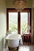 Ein prunkvoller Kronleuchter wertet das klassisch-schlichte Badezimmer mit freistehender Badewanne auf