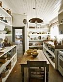 Ei antiker Holztisch in einer Küche mit offenen Schränken
