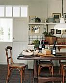 Rustikaler Esstisch und Bistrostühle in einem ehemaligen, zur Küche umgebauten Stall